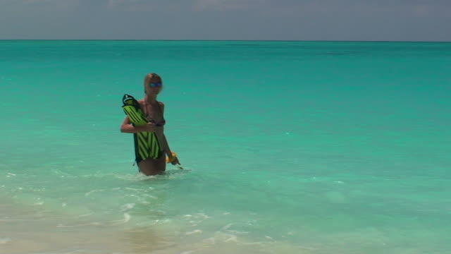 Blond girl walking on the ocean with her fins video