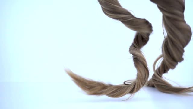 sarı saçlar yavaş hareket halinde düşüyor. - peruk stok videoları ve detay görüntü çekimi