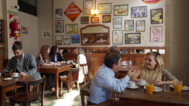 vídeos y material grabado en eventos de stock de mujer de pelo rubio y hombrecito tomando café - comida francesa