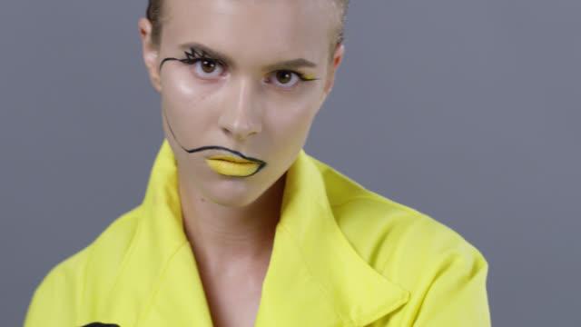 stockvideo's en b-roll-footage met blond high fashion model in heldere fase make-up en zwart lederen handschoenen strijdt. fashion video. - mascara