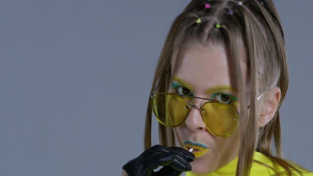 金髮高時尚模特在明亮的舞臺化妝, 戴著黃色的太陽鏡和黑色的皮革手套, 舔棒糖。特寫。時尚視頻。 - 波板糖 個影片檔及 b 捲影像