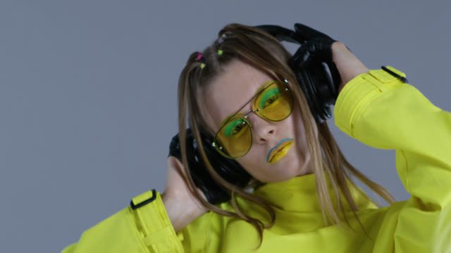 d6dd2a61355b Blond high fashion model in bright stage make-up, wearing yellow sunglasses  and black