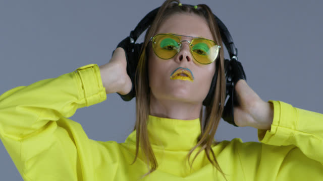 blond high fashion model in bright stage make-up, wearing yellow sunglasses and black leather gloves, listens to music in big wireless headphones. close-up. fashion video. - топ модель стоковые видео и кадры b-roll