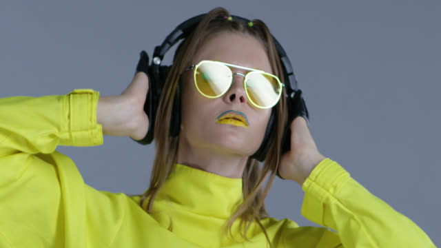 Blond high fashion model in bright stage make-up, wearing yellow sunglasses and black leather gloves, listens to music in big wireless headphones. Close-up. Fashion Video.