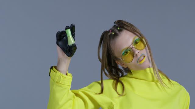 黄色のサングラス、黒革の手袋を身に着けている、明るい舞台メイクの金髪ファッション性の高いモデルは、グリーンのマニキュア液ボトルを示しています。クローズ アップ。ファッション - アイシャドウ点の映像素材/bロール