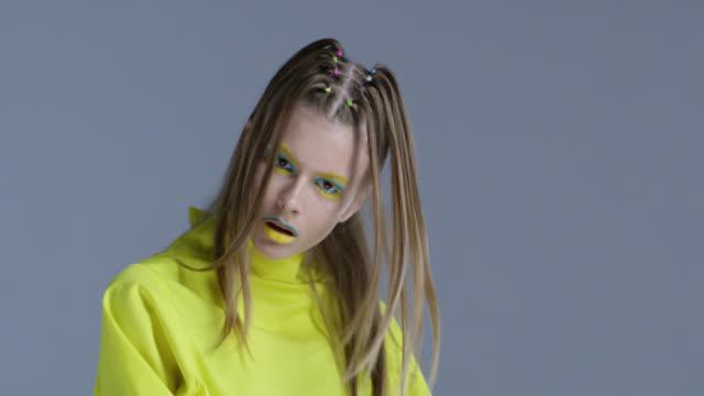 vidéos et rushes de modèle blond haute couture en scène lumineux maquillage jaune et bleu se déplace. mode vidéo. - fard à paupières