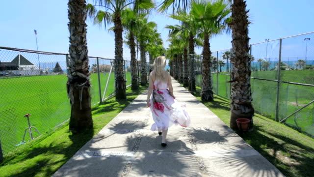 светлый леди ходьбы по берегу моря в виде пальм. - пешеходная дорожка путь сообщения стоковые видео и кадры b-roll