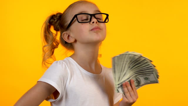 Blond little kid in eyeglasses holding bunch of dollars, first money good income