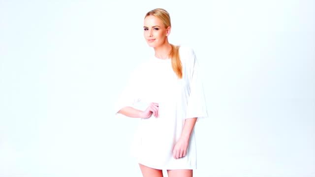 capelli biondi donna in posa naturale in t-shirt bianca - maglietta bianca video stock e b–roll