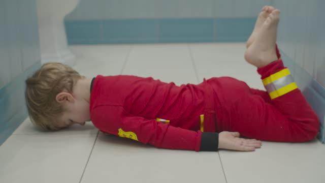 Blond preschool boy in fireman pajamas having fun on bathroom floor. Kid fooling around on white floor.