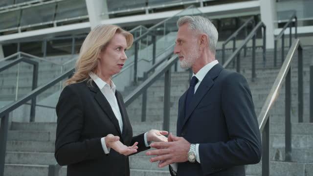 segretaria bionda che sussurra segreto all'orecchio del capo, colleghi che spettegolano al lavoro - ear talking video stock e b–roll