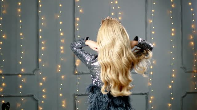 en blond kvinna i en vacker klänning och en krona poserar i studion. röd soffa - lång längd bildbanksvideor och videomaterial från bakom kulisserna