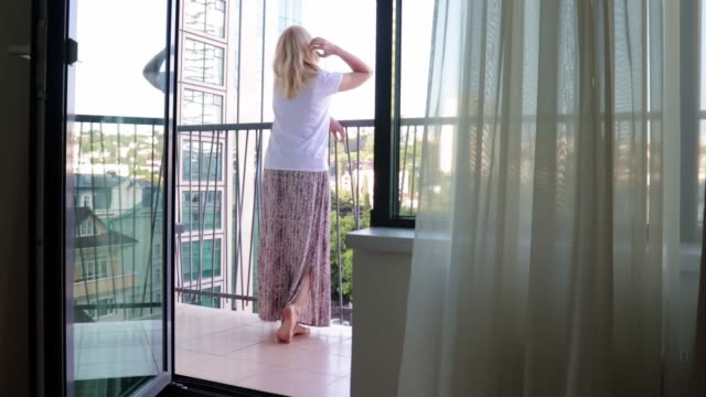 blond woman in a long dress standing on a balcony, looking into the distance, touching her hair and relaxing, view from inside the room through the open door, summer day - terrazza video stock e b–roll