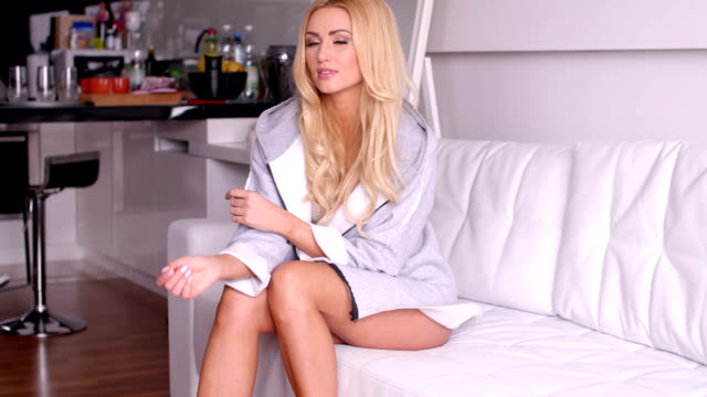 Blond Woman in Sexy Gray Robe Sitting on Sofa Pretty Blond Woman in a Sexy Gray Robe Sitting on a White Sofa While Looking at the Camera Seductively. sweatshirt stock videos & royalty-free footage
