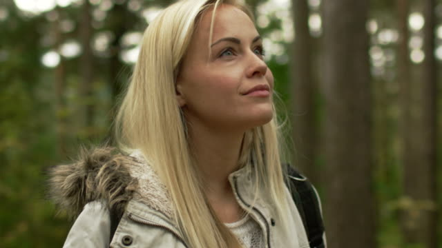 Blond woman in white autumn coat is standing in a forest and looking around.