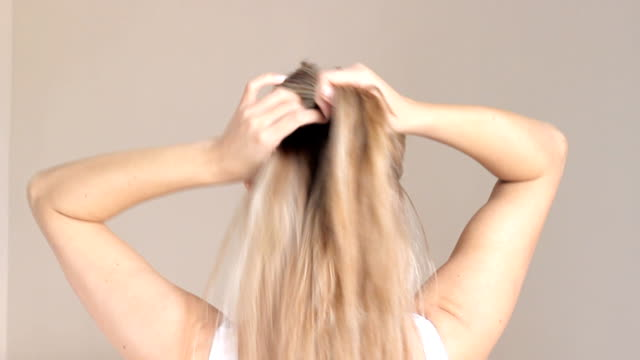 Blond woman plaits her braid. Back view video