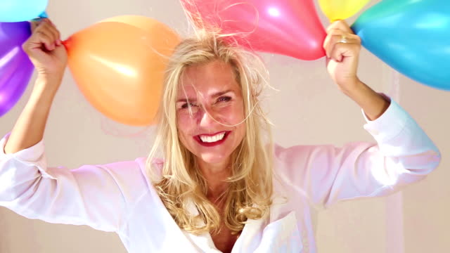 vídeos de stock e filmes b-roll de blond woman playing with a bunch of colorful balloons - mulher balões