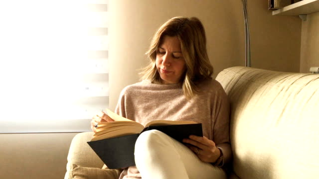 Blond woman reading a book on the couch. Blond woman reading a book on the couch. side lit stock videos & royalty-free footage