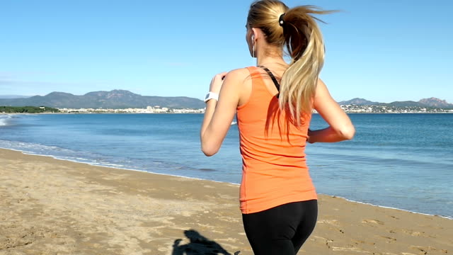 Blond woman running along the sea video