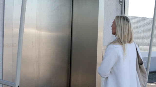blond woman waiting in front of an elevator video