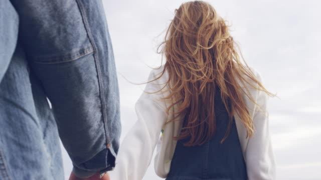 blonde frau mit mann zu fuß, während hand in hand - hände halten stock-videos und b-roll-filmmaterial