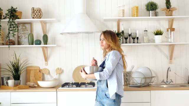 blond woman whisks in bowl on table by stove in kitchen young blond woman whisks in metal bowl on table and dance happily against kitchen utensils on shelves table and stove cooking utensil stock videos & royalty-free footage