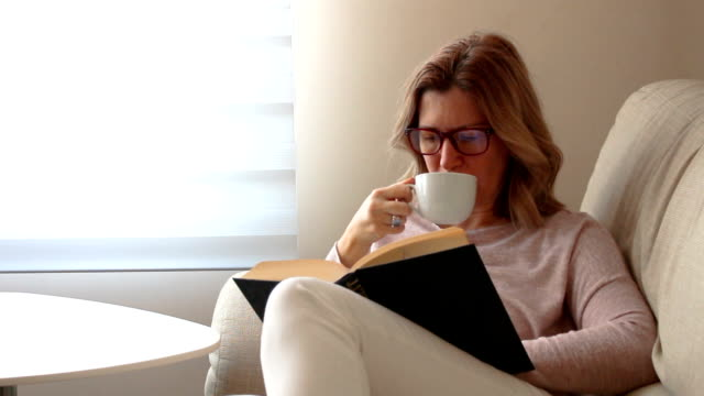 Blond woman with eyeglasses reading a book and drinking coffee Blond woman with eyeglasses reading a book and drinking coffee side lit stock videos & royalty-free footage