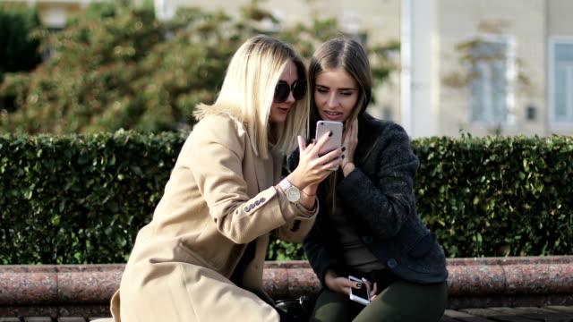 金髪とブルネットを見て携帯電話画面の笑みを浮かべて、公園のベンチの上に座って笑っています。 - ベンチ点の映像素材/bロール