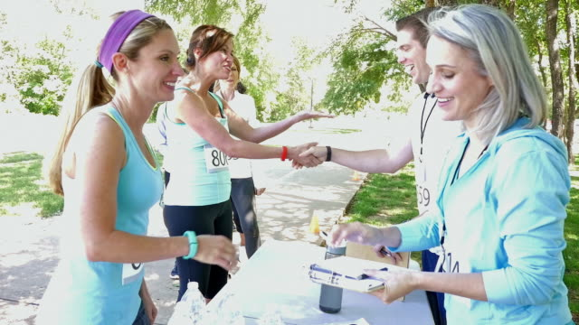 Blonde athletic woman registering for 5k or charity marathon race video