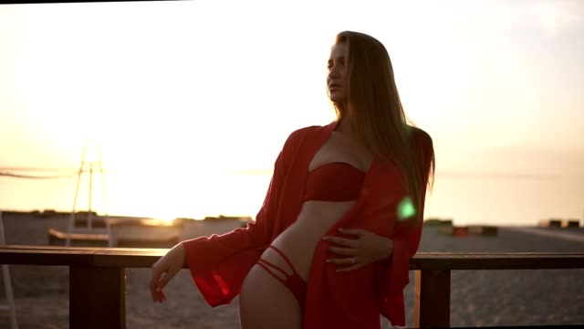 Blonde, attractive woman in red swimsuit and red dressing gown leaning on a wooden railing near the sea. Morning sunrise. Sunlight video