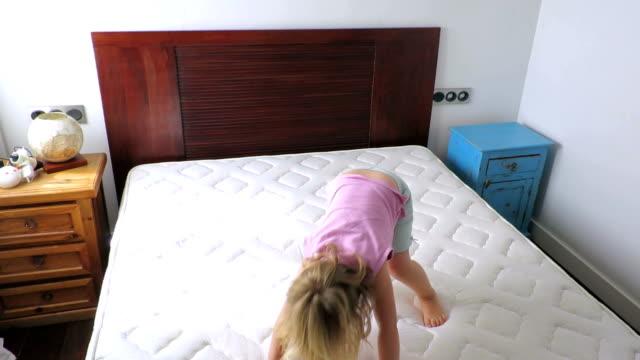 vídeos y material grabado en eventos de stock de bebé rubia saltando sobre el colchón en casa - colchón