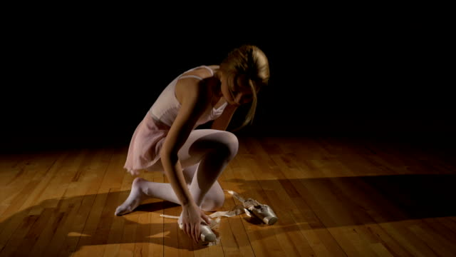 Blonde ballerina untying shoes and sitting on the floor tired - Vidéo