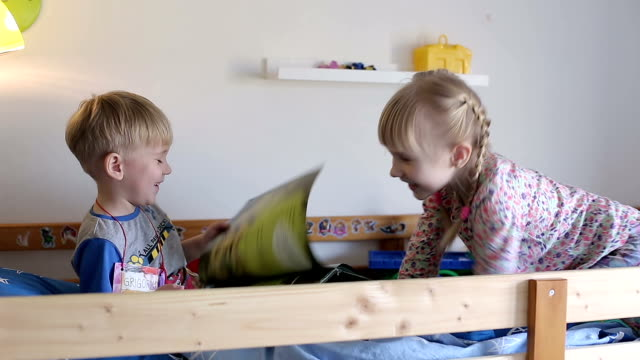 Blonde boy and girl in pajamas are leafing over a pages of a magazine and talking. video