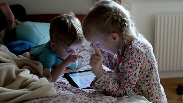 Blonde boy and girl in pajamas are using tablet and talking. video