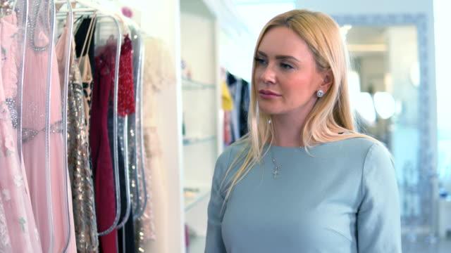 blonde kaukasische weiblichen blick auf kleider. einkaufen in frauen bekleidungsgeschäft. - teurer lebensstil stock-videos und b-roll-filmmaterial