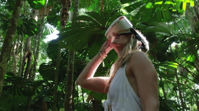 blonde caucasian girl wearing a white vr headset explores a beautiful jungle scene with dappled light. filmed on red camera, slow motion. - ritratto 360 gradi video stock e b–roll