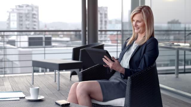 vídeos de stock, filmes e b-roll de mulher caucasiana loira sorrindo e seu tablet digital em um terraço no último piso, na cidade de rolagem - saia