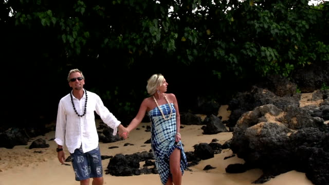 Blonde Couple walking on beach in Hawaii video