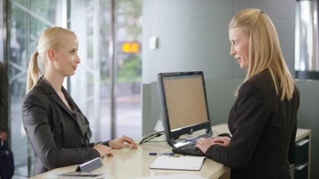 Blonde female customer listening to a female desk clerk advising her video