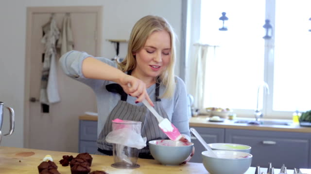 blonde female making cream for decorating cupcakes doing hobby woman puts the cream in