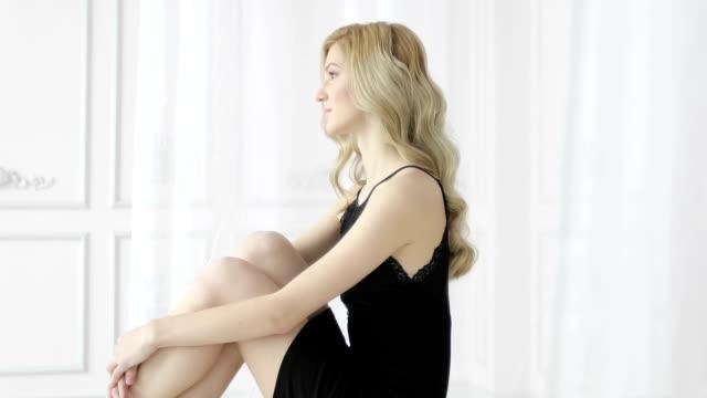 Loiro modelo feminino com cabelo encaracolado em camisa de noite preta sentado numa cama, cortina, abraçando os joelhos dela. - vídeo