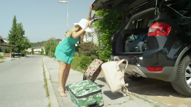 SLOW MOTION: Blonde female opens the boot of her car and suitcases fall out. SLOW MOTION: Blonde female opens the boot of her car and heavy suitcases fall out into the driveway. Young woman overpacked for her summer vacation and she struggles with closing the trunk of the SUV. stuffed stock videos & royalty-free footage
