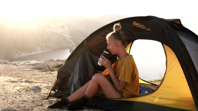 Blonde girl camper sits near the entrance to the tent on the background of mountains and lake. Drinking coffee or tea from a termo mug. Enjoys the vacation. The concept of freedom in the mountains. Wild lifestyle