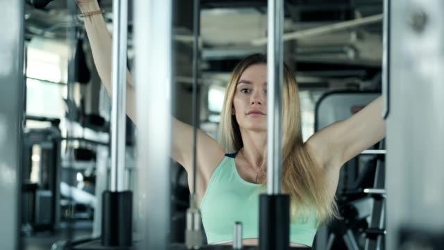 어깨에 대 한 운동을 하 고 금발 소녀. 체육관에서 젊은 여자 리프팅 무게 - 보디 빌딩 스톡 비디오 및 b-롤 화면