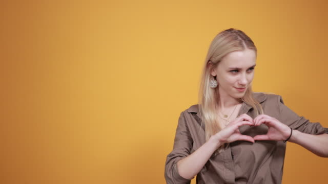 blonde girl in brown blouse over isolated orange background shows emotions