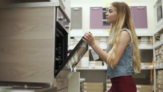 Blonde girl is examining a modern cooker with oven in a shop Young housewife is looking inside a baking oven in a store. She is learning it and touching handles and closing doors, opening kitchen cupboard appliance stock videos & royalty-free footage