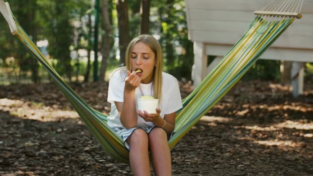 Blonde girl is having a rest while sitting in colorful hammock and eating delicious ice cream with fruits. Summer sunny day in city park. Copy space