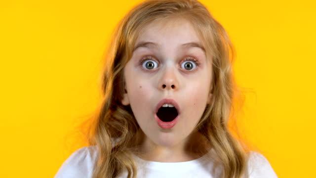 vídeos de stock, filmes e b-roll de menina loura que olha a notícia extremamente choc da audição, fundo amarelo isolado - estupefação