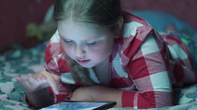 Blonde girl playing game on tablet and lying on the sofa in the evening. 4k Close up of face and hands of 8 years old kid playing computer games lying in his bed in evening. Child using tablet pc fat nutrient stock videos & royalty-free footage