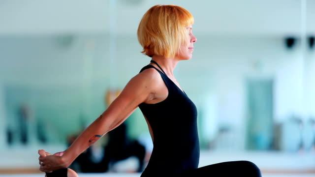 blonde mädchen praktizieren yoga auf der matte in der nähe des spiegels - haarfarbe stock-videos und b-roll-filmmaterial